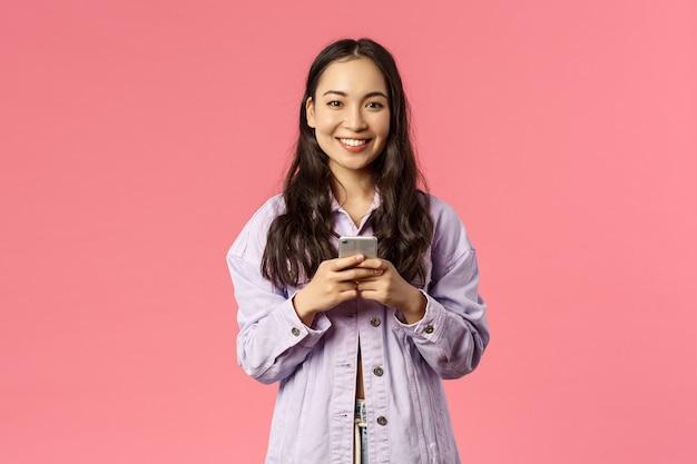 Concept de mode de vie, de personnes et de beauté en ligne. jeune fille élégante et gaie utilisant un téléphone portable et souriante heureuse devant la caméra, discutant pendant le verrouillage, utilisant l'application éducative, fond rose