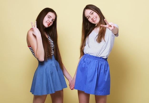 Concept de mode de vie et de personnes: deux jeunes amies debout ensemble et s'amusant. regardant la caméra fond jaune.