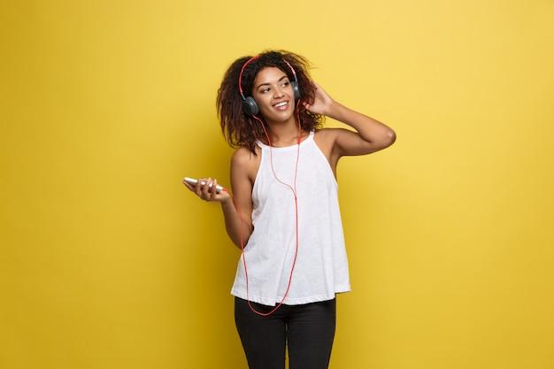 Concept de mode de vie - portrait d'une belle femme afro-américaine joyeuse écoutant de la musique sur un téléphone portable. contexte en pastel pastel jaune. espace de copie.