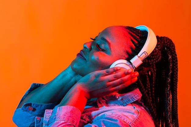 Concept de mode de vie - portrait de la belle femme afro-américaine joyeuse écouter de la musique.
