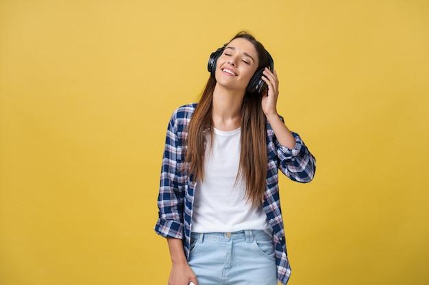 Concept de mode de vie - portrait de belle femme caucasienne joyeuse écoutant de la musique sur téléphone mobile. fond de studio pastel jaune. copiez l'espace.