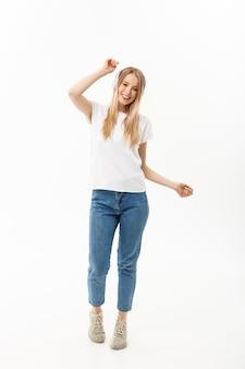 Concept de mode de vie : portrait d'une étudiante joyeuse et heureuse écoutant de la musique avec des écouteurs tout en dansant isolée sur fond blanc