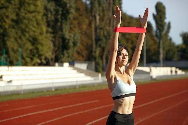 Concept de mode de vie sain : belle femme en forme faisant des exercices avec une bande de résistance au stade. espace pour le texte