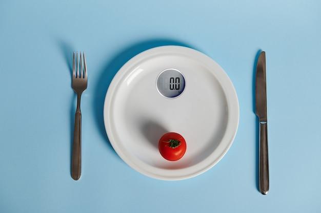 Le concept d'un mode de vie sain et d'une bonne nutrition. couverts et tomates sur une assiette sous forme d'échelles de mesure