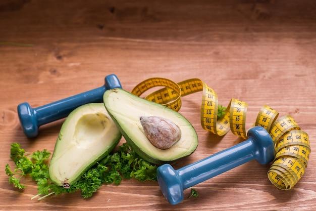 Concept de mode de vie sain et d'habitudes saines avocat vert et haltères sport et alimentation saine