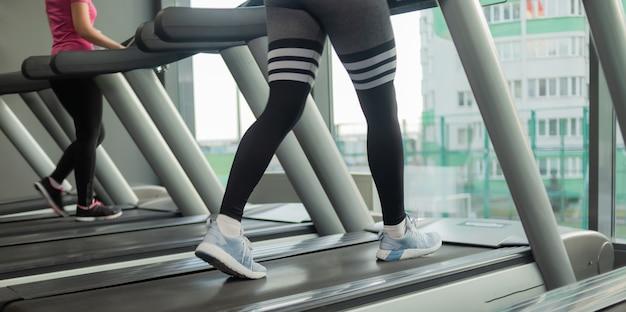Concept de mode de vie sain. les jambes des femmes s'exécutent sur un tapis roulant dans la salle de sport