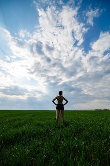 Concept de mode de vie sain. une jeune femme séduisante en tenue de sport s'étire la main avant de s'entraîner sur la nature contre un ciel bleu. échauffement musculaire
