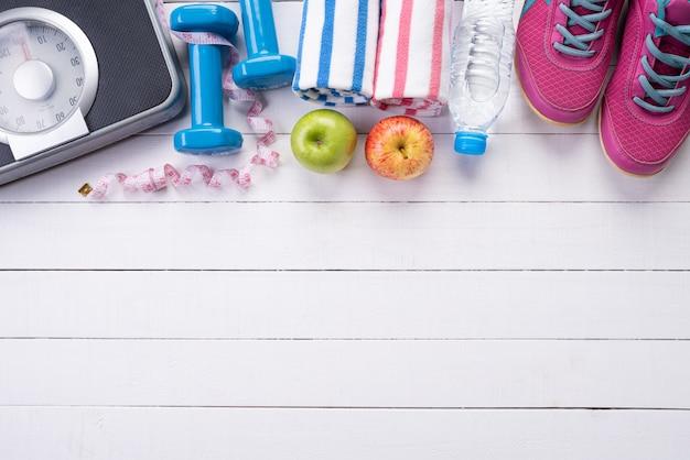 Concept de mode de vie sain, de nourriture et de sport sur bois blanc.