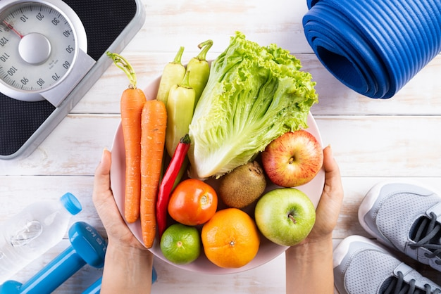 Concept de mode de vie sain, de nourriture et de sport sur un fond en bois blanc.