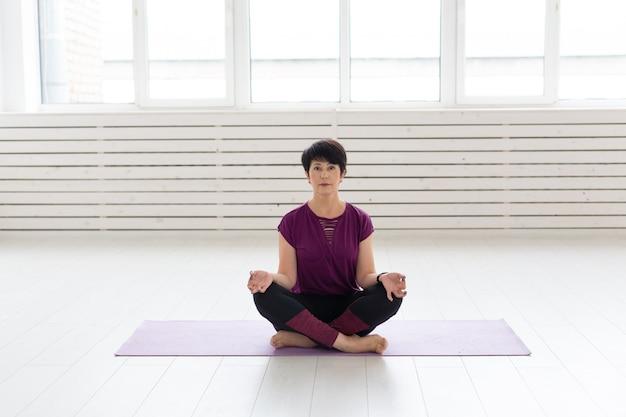 Concept de mode de vie sain, de personnes et de sport - jolie femme d'âge moyen pratiquant le yoga en posture de lotus