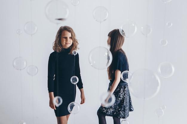 Le concept d'un mode de vie sain, la protection des enfants, le shopping - un adolescent jouant ensemble. enfants heureux: soeurs sur fond blanc