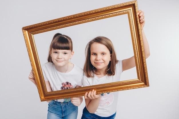 Le concept d'un mode de vie sain, la protection des enfants, le shopping - ce sont des adolescents qui jouent ensemble. enfants heureux: sœurs image en direct - les filles regardent hors du cadre