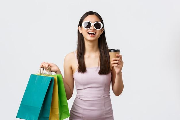 Concept de mode de vie, de shopping et de tourisme. femme asiatique heureuse réussie, entrepreneur achetant de nouveaux