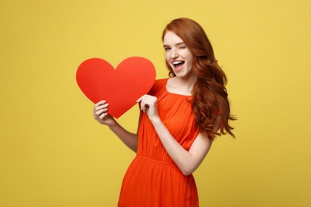 Concept de mode de vie et de vacances - portrait jeune femme heureuse aux cheveux roux en belle robe orange tenant du papier grand coeur rouge.
