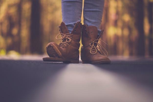Concept de mode de vie de voyage - point de vue au sol avec route goudronnée défocalisée et gros plan sur une vieille paire de chaussures de marche de trekking cassées