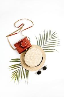 Concept de mode de voyage d'été. paille, appareil photo rétro, lunettes de soleil et feuille de palmier tropical