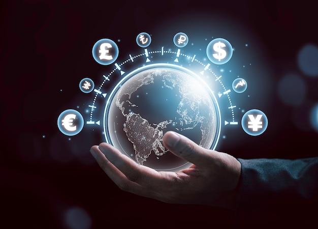 Concept mondial d'échange de devises, homme d'affaires tenant un monde avec effet de ligne virtuelle et signe dollar yuan yen euro et livre sterling.