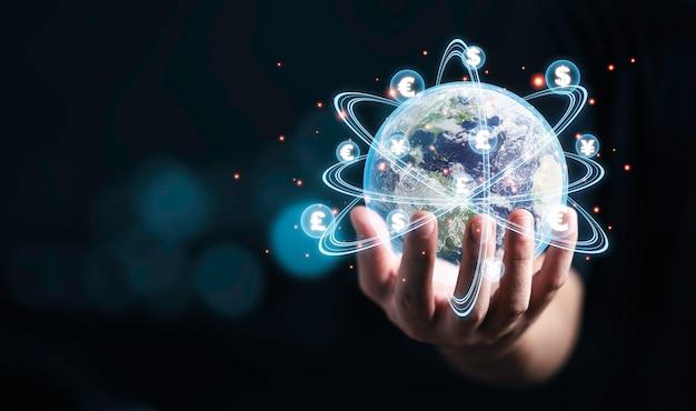 Concept mondial d'échange de devises, monde tenant la main avec effet de ligne virtuelle et signe dollar yuan yen euro et livre sterling.