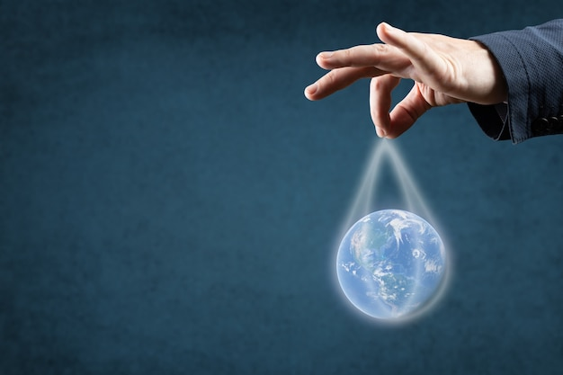 Concept de mondialisation, d'énergie et d'écologie. la main de l'homme en costume tient la planète terre par les ficelles