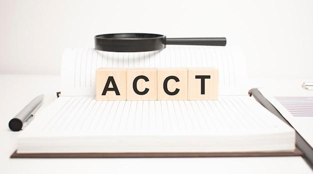 Concept de mot d'acc. cubes en bois, bloc-notes, stylo et tableaux d'affaires.