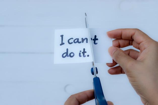 Concept de motivation, mains de femme tenant une carte je peux le faire avec des ciseaux.