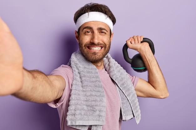 Concept de musculation. heureux l'homme mal rasé fait du sport avec du poids