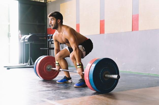 Concept de musculation avec l'homme sur le point de lever l'haltère