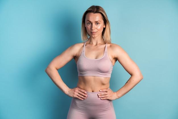 Concept de musculation et de sport. jeune jolie femme en forme aux cheveux courts vêtue de vêtements de sport mettant ses bras dans la taille et posant contre un mur blanc bleu