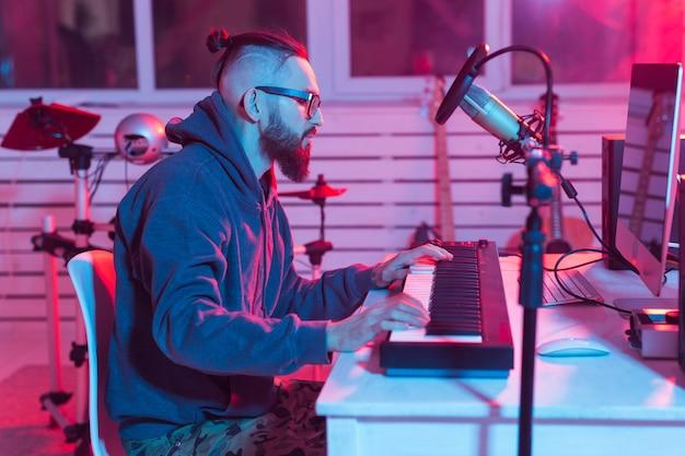 Concept de musicien et de création musicale - producteur sonore masculin travaillant dans un studio d'enregistrement.