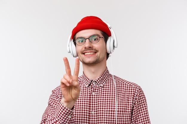 Concept de musique, de technologie et de personnes. les mecs de la paix. joyeux hipster mignon homme dans des verres et chemise à carreaux, porter des lunettes en écoutant de la musique dans les écouteurs rester positif, sourire et montrer la bonne volonté
