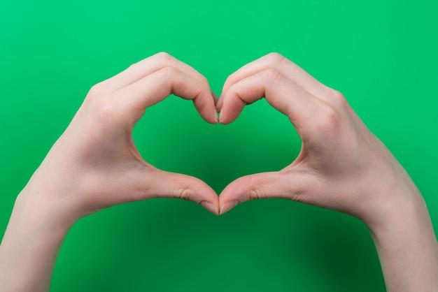 Concept de nature d'amour. top pov au-dessus des frais généraux vue rapprochée photo de femme faisant coeur avec ses mains isolées sur fond vert