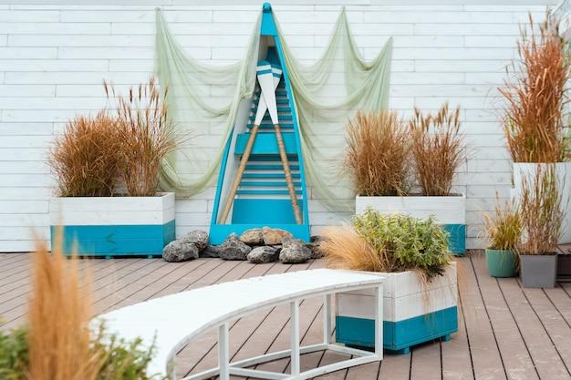 Concept nautique avec filet de pêche décoratif, bateau en bois et pagaies. emplacement extérieur de style marin pour une séance photo.