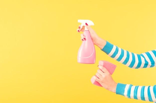 Concept de nettoyage à domicile. services de nettoyage. mains tenant un atomiseur et une éponge. copiez l'espace sur fond jaune.