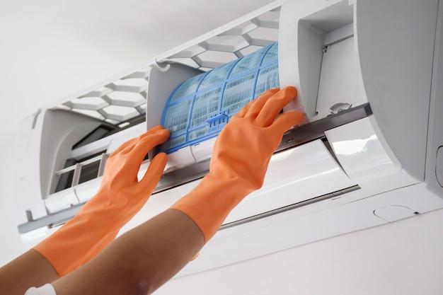 Concept de nettoyage de filtre de climatiseur de prise de main d'homme asiatique