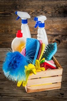 Concept de nettoyage de printemps avec des fournitures, pile de produits de nettoyage de maison. concept de corvée domestique, sur fond de bois rustique ou jardin copie espace