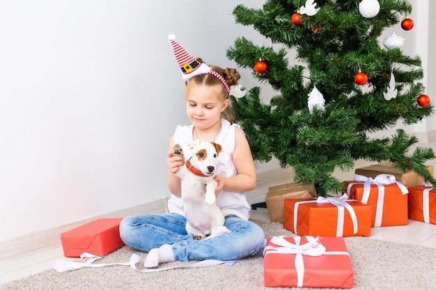 Concept de noël, animaux de compagnie et vacances - enfant en bonnet de noel avec un chiot jack russell terrier