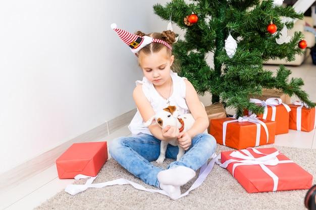 Concept de noël, d'animaux et de vacances - enfant en bonnet de noel avec un chiot jack russell terrier.
