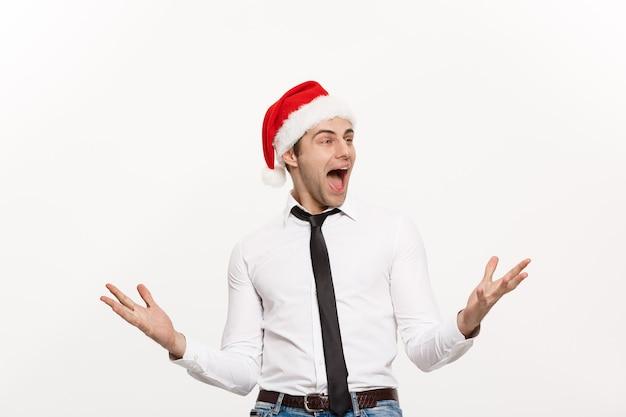 Concept de noël - bel homme d'affaires porte bonnet de noel posant avec une expression faciale surprenante sur un mur blanc isolé.