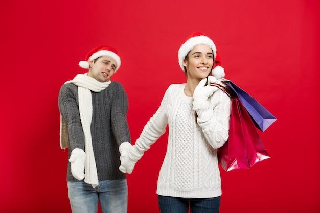 Concept de noël - belle petite amie oblige son petit ami à faire du shopping sur le mur de noël rouge.