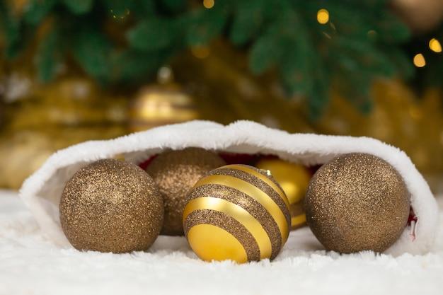 Concept de noël. boules dorées en chapeau de père noël