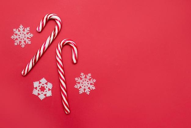 Le concept de noël avec canne en bonbon à rayures sur fond rouge, carte de voeux, espace de copie