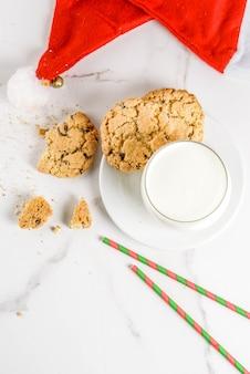 Concept de noël, carte de voeux. verre à lait et biscuits pour le père noël avec chapeau de père noël sur scène en marbre blanc