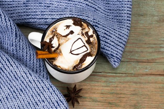 Concept de noël, chocolat chaud ou cacao avec des guimauves et des épices, cadeaux de noël, cannes de bonbon, branche d'arbre de noël et pommes de pin, sur une vieille table en bois rustique