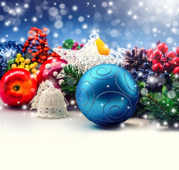 Concept de noël composé d'une boule bleue, de belles pommes, de petites branches d'arbres, d'étoiles et d'arrière-plan flou.