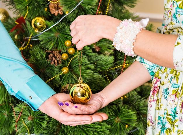 Concept de noël, décoration, vacances et personnes - gros plan des mains tenant la boule d'or de noël