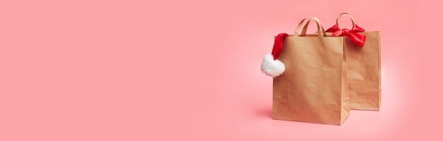 Concept de noël, deux sacs en papier avec chapeau de noël, sur fond rose, bannière, espace copie, maquette