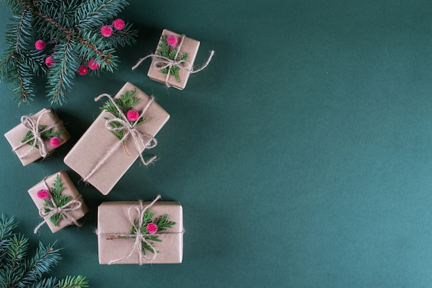 Concept de noël emballage de cadeaux en papier kraft beige vintage et décor naturel. branches de sapin et de fruits rouges. vue de dessus à plat