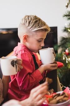 Concept de noël avec un garçon buvant du thé
