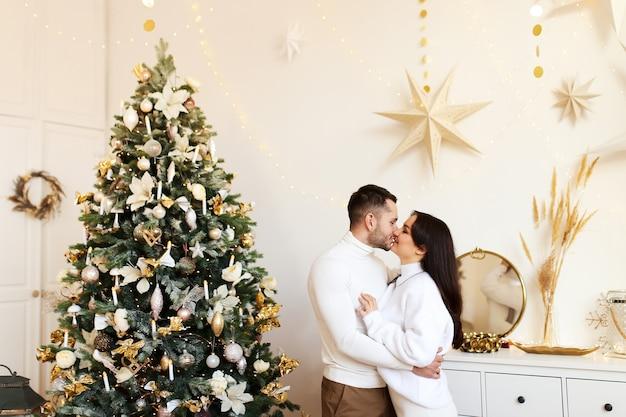 Concept de noël heureux, couple amoureux étreindre et s'embrasser par l'arbre de noël