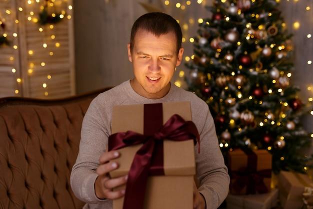 Concept de noël et de magie - portrait d'un jeune homme surpris heureux ouvrant une boîte-cadeau dans une pièce sombre décorée avec un arbre de noël et des lumières led de vacances